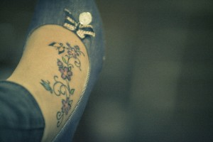 Feminine butterfly and flowers on foot tattoos