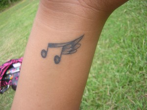 Music note with wings tattoo