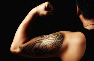 tribal arm tattoo on man