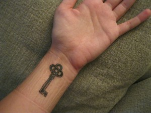 Simple key tattoo on the wrist