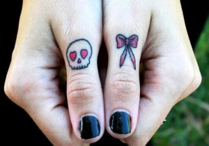 Skull and Bow Thumb Knuckle Tattoo